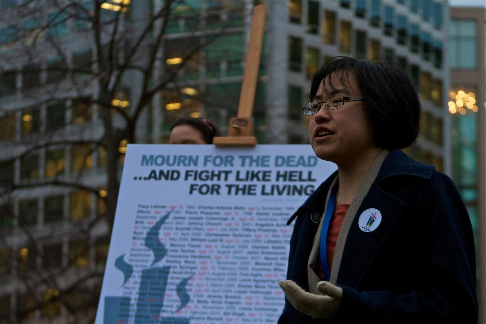 Photo of Lydia Brown, a young East Asian person, gesturing and speaking somberly outside in front of a poster that says Mourn For The Dead And Fight Like Hell For The Living. Credit to Kory Otto-Jacobs.