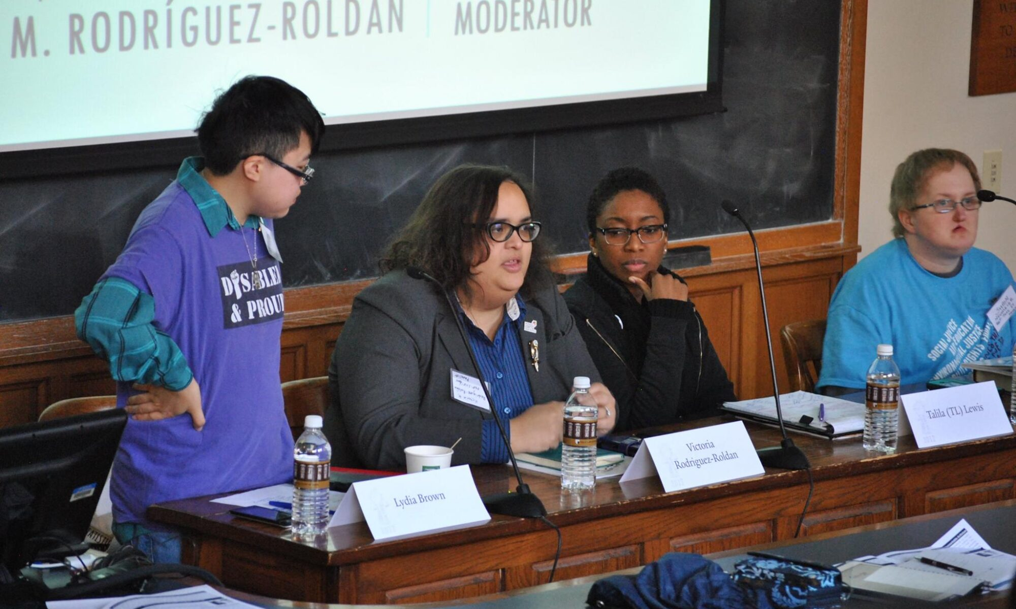 Photo of Lydia Brown (a young East Asian person), Victoria Rodríguez-Roldán (a young Latina woman), Talila Lewis (a young Black person), and Shain Neumeier (a young white person) sitting at the front of a wood-paneled classroom.